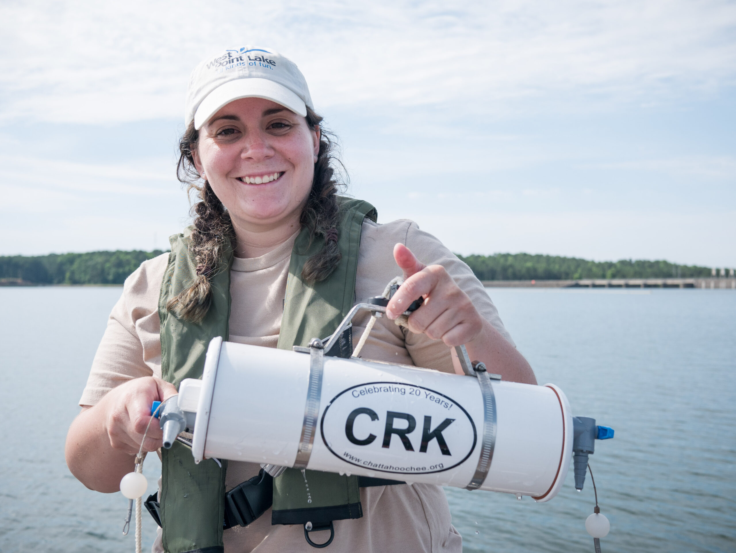 Woman on boat holds water sampling device with CRK sticker
