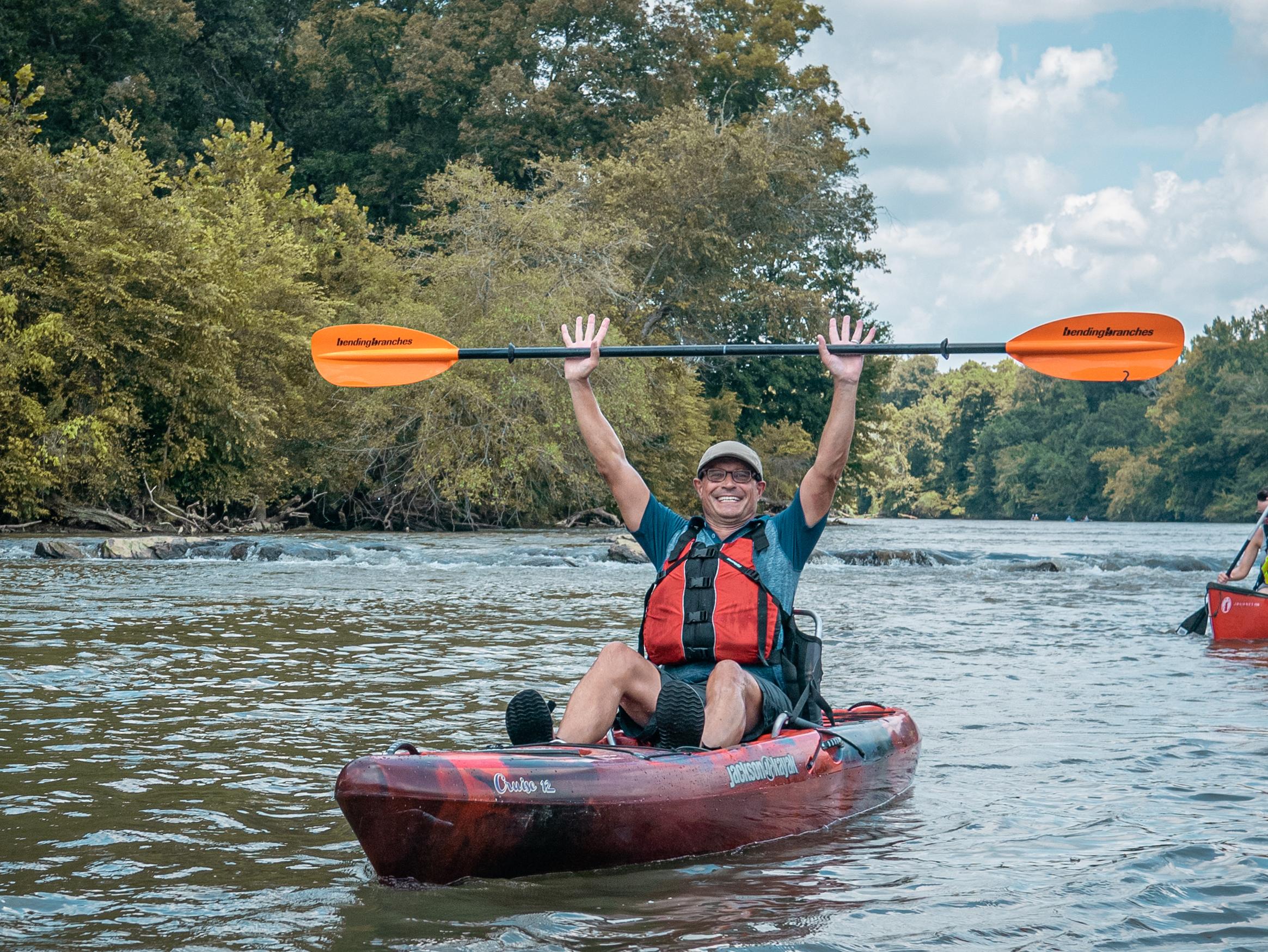 Man in kayak raises paddle and smiles