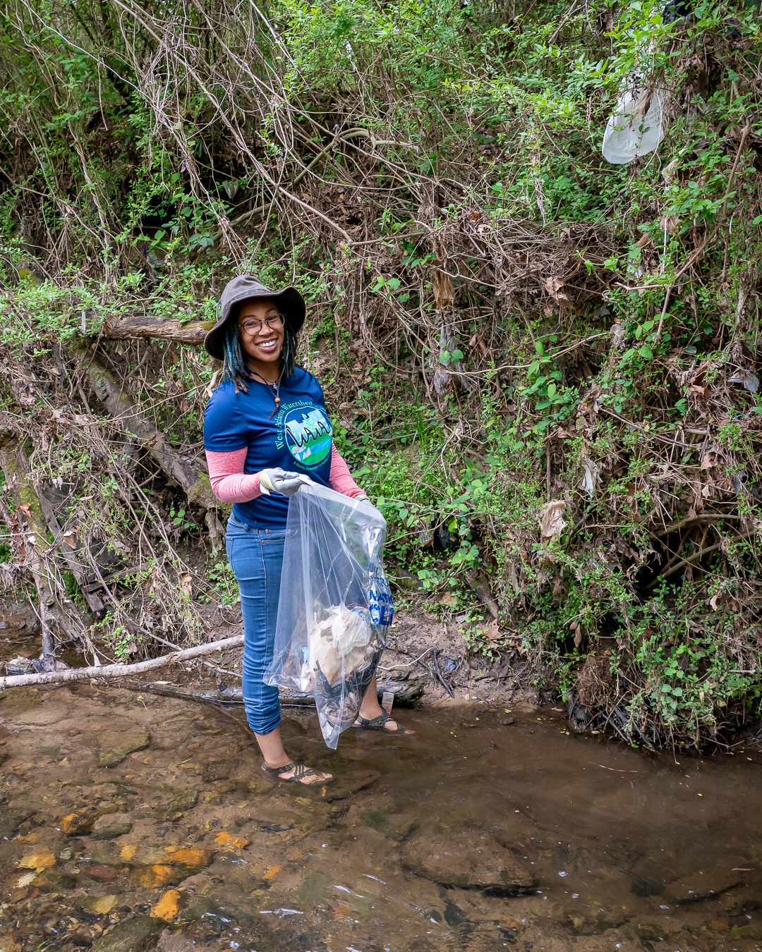 Woman in creek with bag of trash