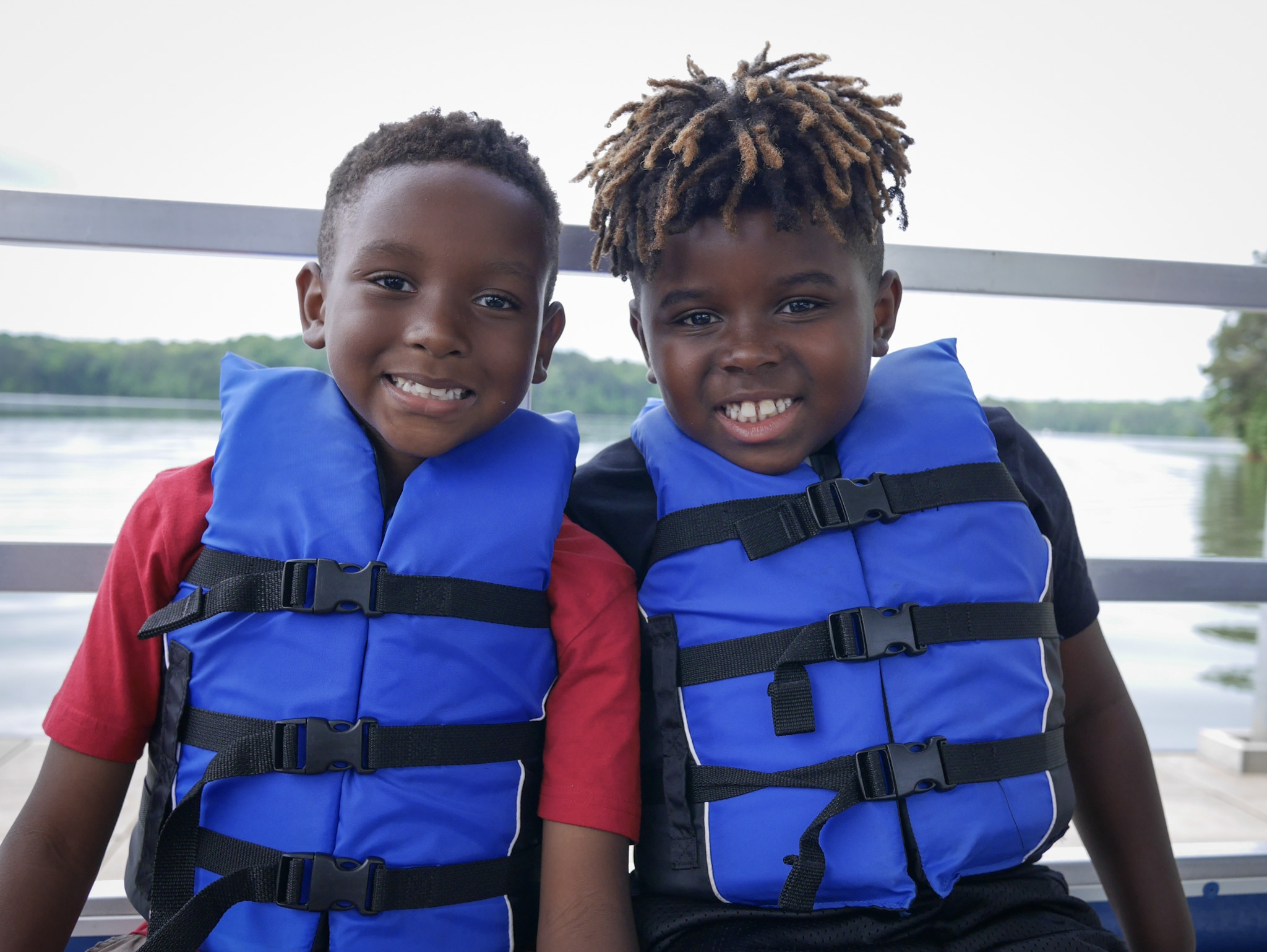 Two children in lifejackets on boats smile