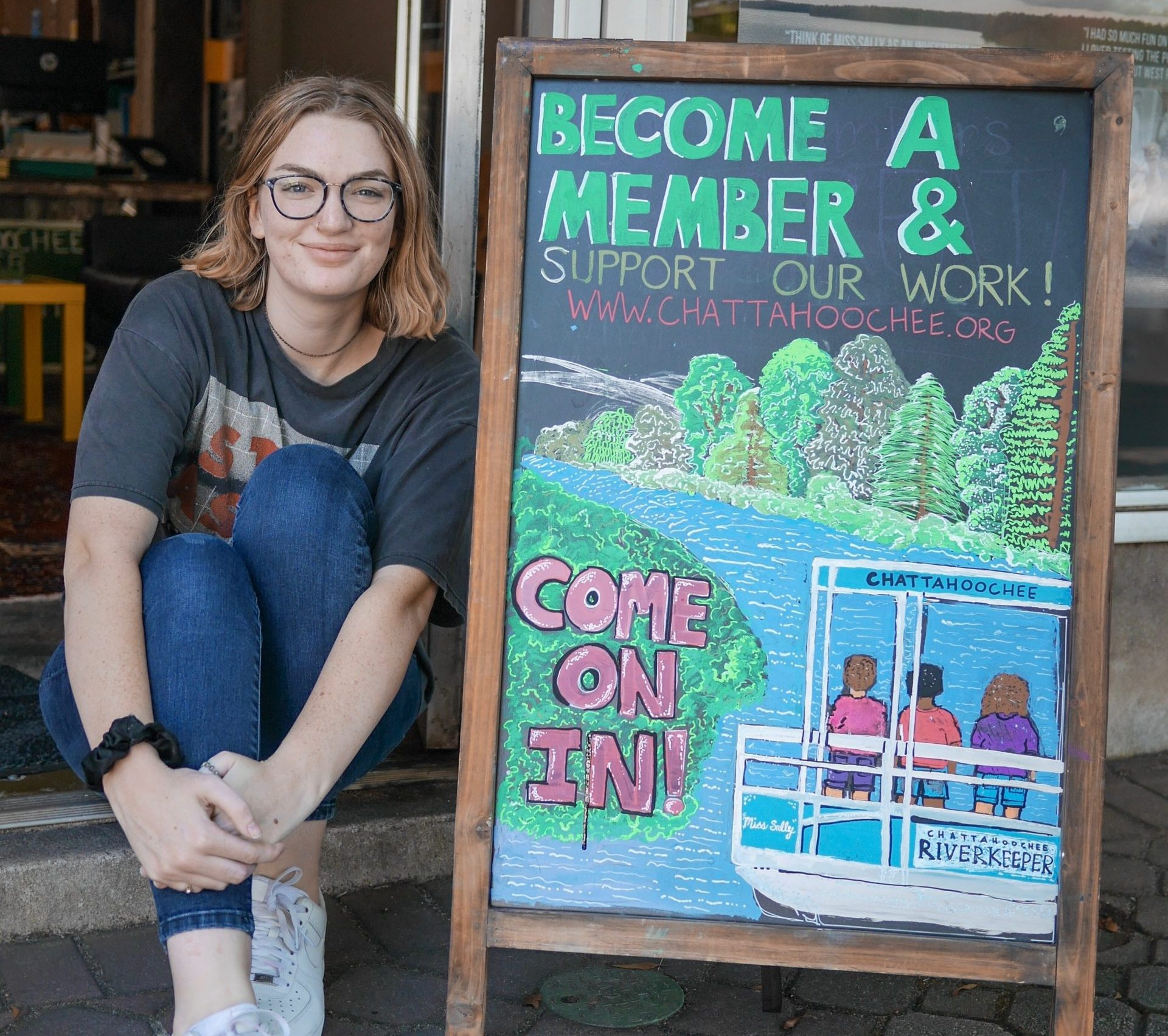 """Woman sits on sidewalk next to chalkboard that says """"become a member"""""""