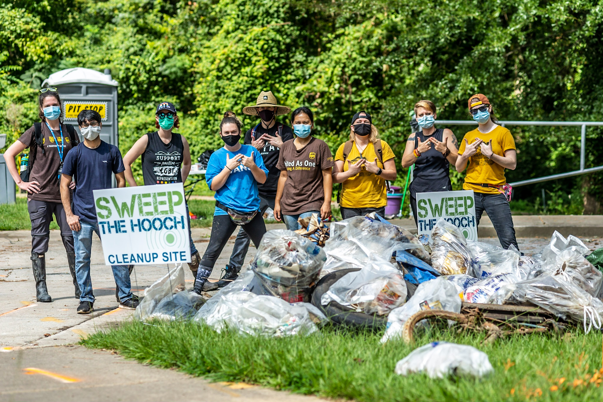 Volunteers gather around trash they've gathered next to sign that says Sweep the Hooch